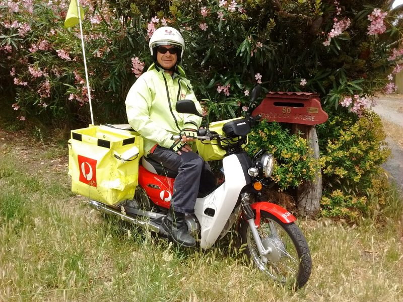 "Letter carrier on a 110cc Honda ""Postie"" motorbike in Willunga, Australia."